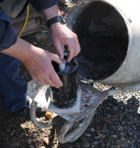 Place perforated pipe over base and fill with two handfuls of mixture